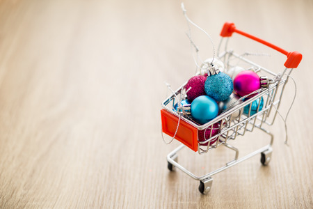 Christmas balls in shopping cart  box on wooden table. Reklamní fotografie