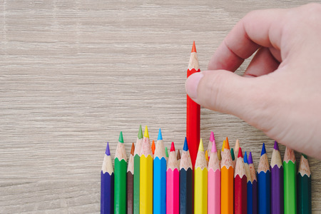 Hand choosing a colored pencil on wooden background.