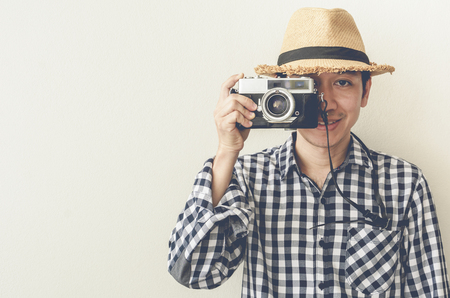 say cheese: Portrait of a smiling asian man taking photo on retro camera on white background.