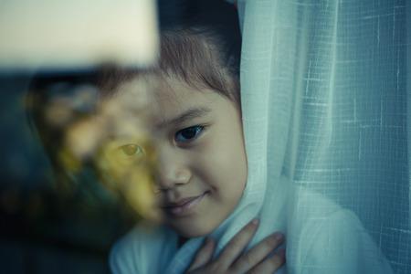 ガラス窓の後ろに小さな女の子。ビンテージ トーン