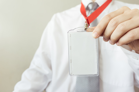 Man holding Identification white blank plastic id card. Stock Photo
