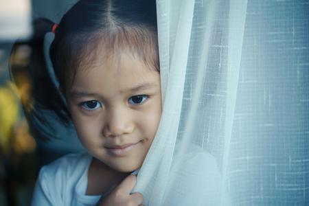 The little girl behind a glass window. vintage tone Фото со стока
