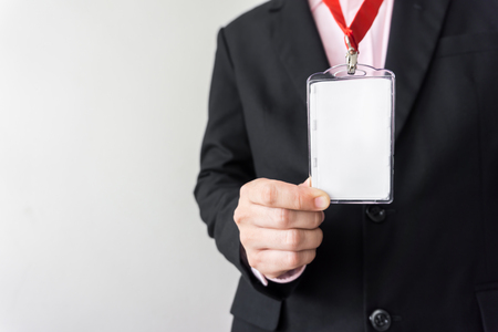 clasps: Man holding Identification white blank plastic id card. Stock Photo