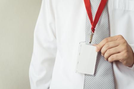 attachment: Man holding Identification white blank plastic id card. Stock Photo
