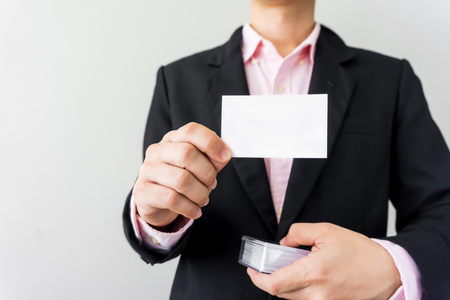 attachment: Man holding white business card