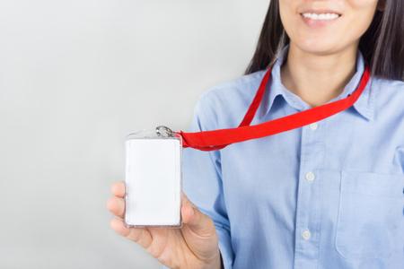 Woman holding Identification white blank plastic id card.