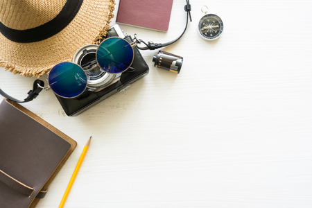 Top view of wooden table with accessories, passport, notebook, film camera, wicker hat and sunglasses on wooden table - travel concept. Reklamní fotografie