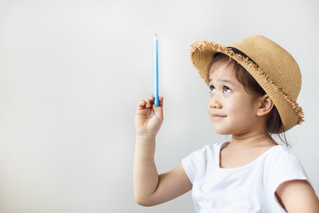 A happy asian girl with color pencils in hand. Learning, education concept. Reklamní fotografie