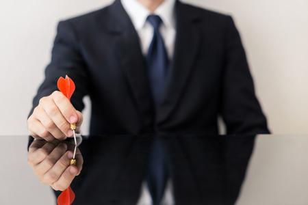 Businessman holding a dart  - business targeting, aiming, focus concept. Foto de archivo