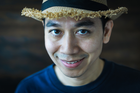 Portrait of a smiling  young Asian man wearing straw hat.