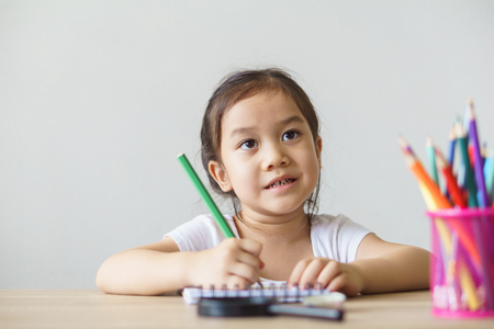 A pretty asian girl drawing, writing. Learning, education concept.