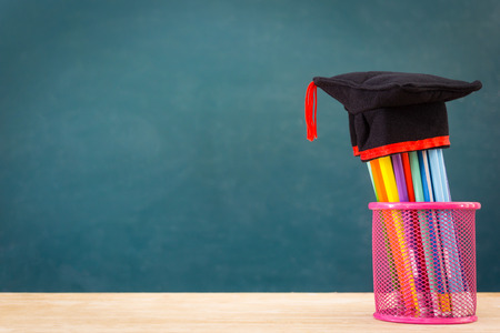 Pencils and graduation hat Concept of education or back to school on green background