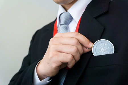 Businessman holding a compass  - business targeting, aiming, direction, focus concept.