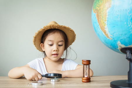 A pretty asian girl using magnifying glass. Learning, education concept.