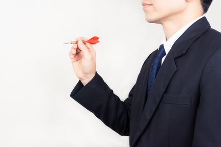 Businessman holding a dart  - business targeting, aiming, focus concept. Banque d'images