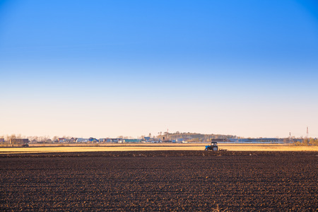 clear day: Tractor plowing a field for spring planting in clear day