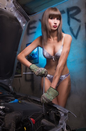 Girl in the garage with the tools in heavy boots and underwear photo