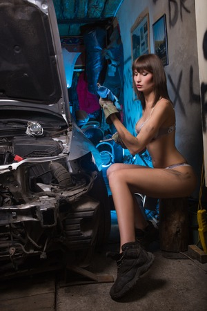 Girl in the garage with the tools in heavy boots and underwear Standard-Bild