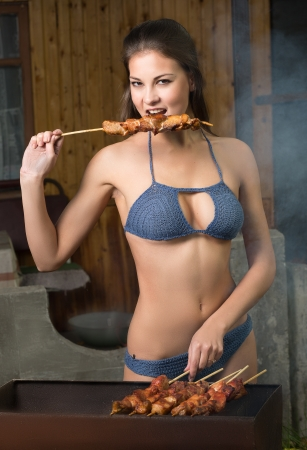 shish kebab: girl cooks meat on a barbecue grill Stock Photo