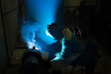 welder in protective mask weld details. sparks fly photo