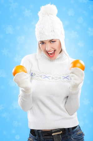 beautiful girl in winter hat with oranges. on snow background photo