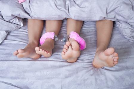 セクシーなカップルはキスをし、ベッドの中で遊んでのクローズ アップ
