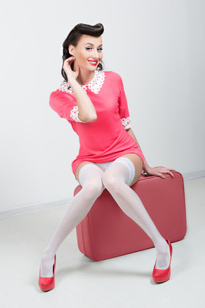 PinUp sexy girl with pink suitcase   photo