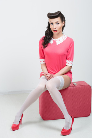 sit up: PinUp sexy girl with pink suitcase   Stock Photo