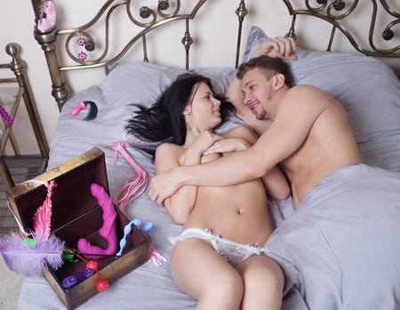 sex: сексуальная пара, лежа в постели Фото со стока