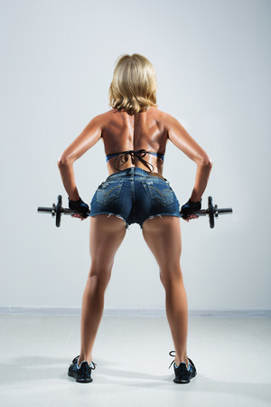 back and hands of a young sporty muscular woman working out with two dumbbells photo