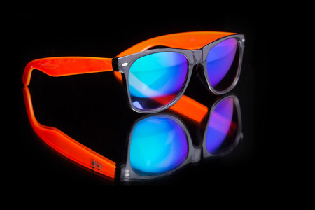 colored sunglasses. on a dark background with reflection Stock Photo