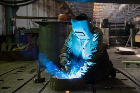 welder works in a factory in the helmet. photo