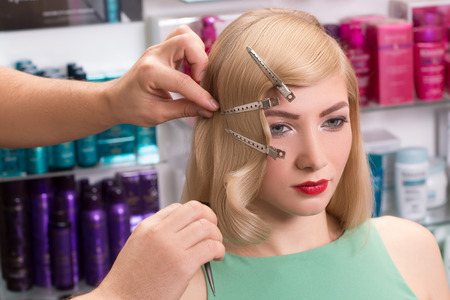 hairstylist makes hairstyle for beautiful girl photo