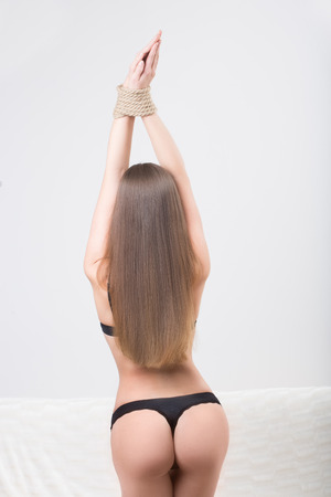 sex toy: model tied up with fetish restraint rope.