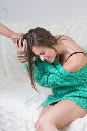 Man hitting a young woman.  hands are tied Stock Photo