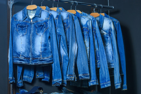 clothing rack: fashion jeans jacket on hangers at the show