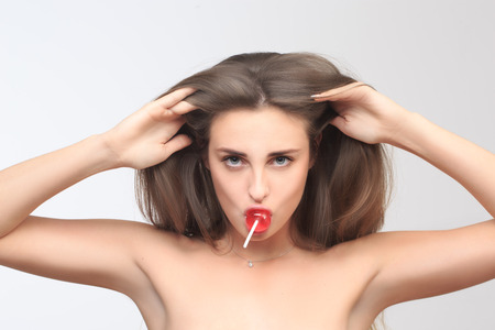 erotically: girl with beautiful hair sucks a lollipop. Stock Photo