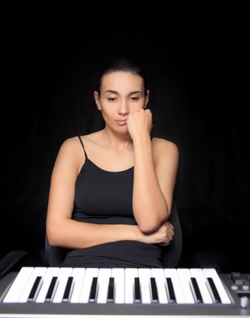 keyboard instrument: emotional woman learning to play the piano. Stock Photo