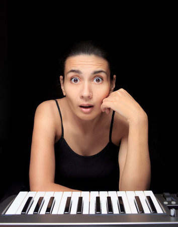 emotional woman learning to play the piano. photo