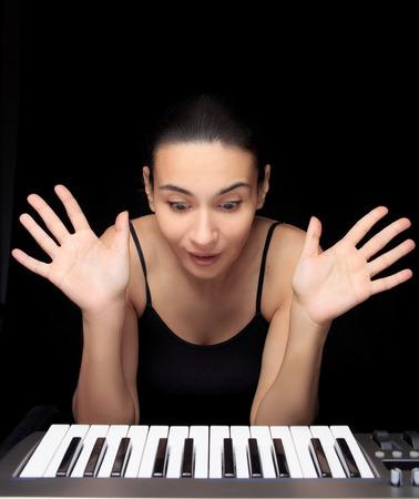 tocando piano: Mujer emocional aprender a tocar el piano. Foto de archivo
