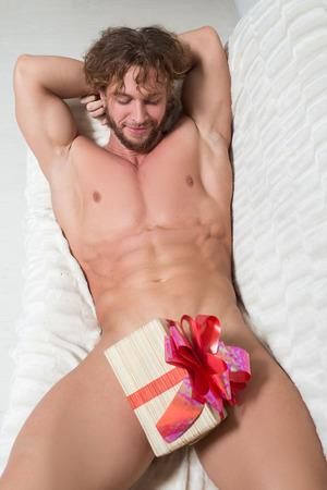 sexo: hombre desnudo en un sofá con un regalo