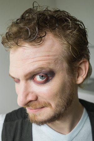 cunning: cunning man with red painted eyes. Stock Photo