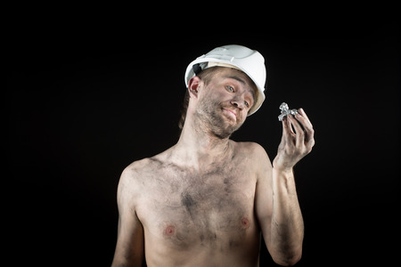 the miner: miner shows a silver nugget Stock Photo
