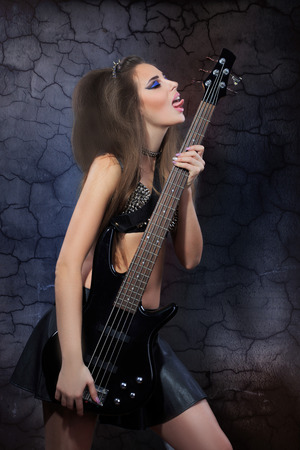 Woman playing music on a bass guitar photo