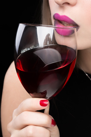 woman with glass red wine. saturated color, nails. Foto de archivo