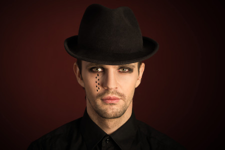 a young man  with  make  up and painted tears. photo