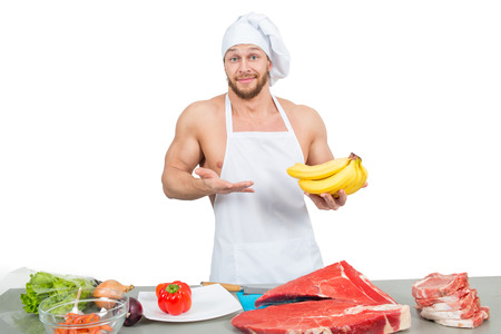 chef in a white apron holding bananas