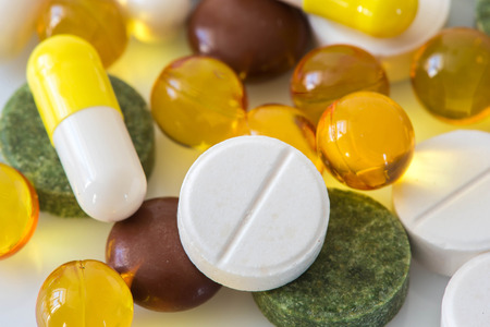 health care decisions: Pile of various colorful pills isolated on white