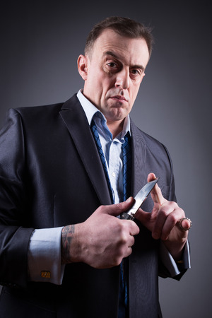 gangster: male gangster in a business suit with a knife Stock Photo