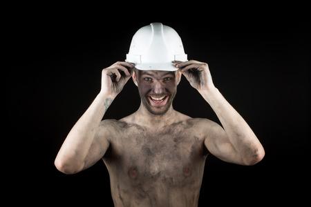metallurgist: Happy dirty worker in helmet. Stock Photo